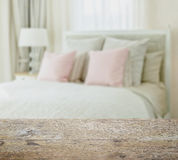 Wooden table top with blur of luxury bedroom interior with pink pillows Royalty Free Stock Photos