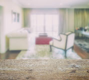 Wooden table top with blur of luxury living room interior Royalty Free Stock Photo