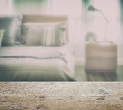 Wooden table top with blur of modern bedding with reading lamp Stock Images