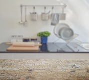 Wooden table top with blur of modern ceramic kitchenware and utensils. On the countertop stock image