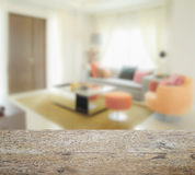 Wooden table top with blur of modern living room interior with orange tone. Decoration Royalty Free Stock Photography