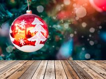 Wooden table top on blurred Christmas ball on tree with snow shi. Wooden table top on blurred Christmas ball on tree with snow and shine Royalty Free Stock Photos