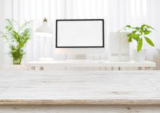 Wooden table top with blurred modern working place as background royalty free stock photography
