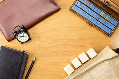 Wooden Table top with  clock,type box,notebook,leather bag and p Stock Image