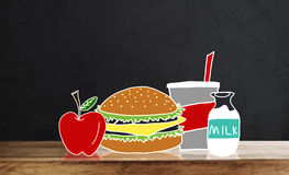 Wooden table top with drawing breakfast, Hamburger, apple, juice and milk, on black wall backgrounds Stock Photos