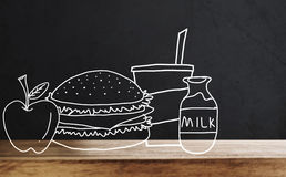 Wooden table top with drawing breakfast, Hamburger, apple, juice and milk, on black wall backgrounds Stock Image