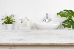 Wooden table top over blurred bathroom interior and spa products.  stock photography