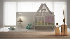 Wooden table top or shelf with aromatic sticks bottles over blurred child`s room with cradle, carpet and bed side table, white ar. Chitecture interior design stock images