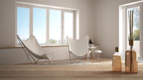 Wooden table top or shelf with aromatic sticks bottles over blurred modern living room with carpet and armchairs. White architecture interior design royalty free stock images