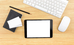 Wooden table top with tablet,black notebook,pencil,keyboard and Royalty Free Stock Photos
