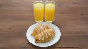 On the wooden table are two glasses of orange juice and a plate with croissants. The camera moves from left to right stock footage