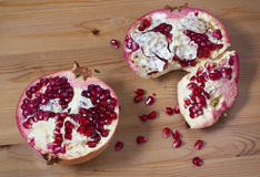 On a wooden table two halves of pomegranate lying Royalty Free Stock Photo