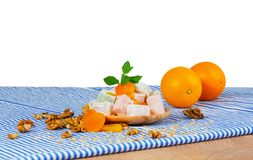 A wooden plate of Turkish delight or lokum, walnuts, dried apricots and sappy oranges isolated on a white background. A wooden table with two juicy oranges, a Stock Photo