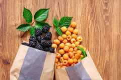 Two paper bags with yellow raspberries and blackberries. Stock Image