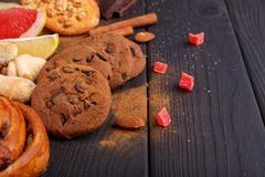On the table, various fragrant bakes,, chocolate slices, candied fruits and citrus. Inside. Stock Images