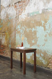 Wooden table with vase and wallnuts near old plastered wall Stock Photos