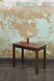 Wooden table with vase and wallnuts near old plastered wall Stock Images