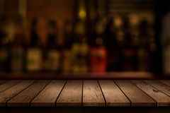 Wooden table with a view of blurred beverages bar. Backdrop royalty free stock image