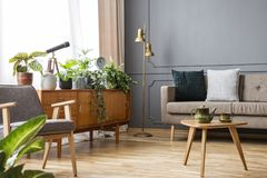 Wooden table in vintage living room interior with cabinet betwee Royalty Free Stock Images