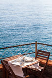 Wooden table with white, dishwater and chairs on ocean in a rest Stock Image
