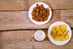 On a wooden table are white plates with crispy croutons and potato chips. Horizontal frame royalty free stock photos