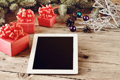 On the wooden table white tablet with Christmas presents closeup Royalty Free Stock Photos
