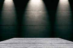 Wooden table with wood wall in dark room illuminated by 3 spots Stock Images
