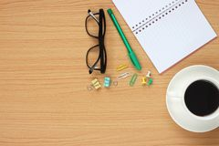 The wooden table working have a coffee mug around a blank book a stock image