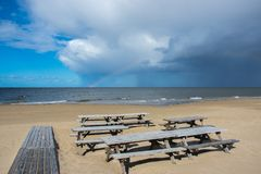 Wooden tables and benches of a summer cafe on a deserted beach in the bright sunny day of the beginning of autumn royalty free stock photo