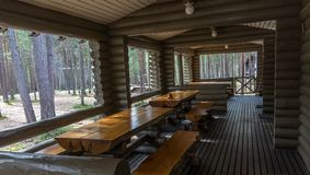 Wooden tables and benches on the terrace of a log house. In the forest Royalty Free Stock Photo