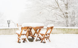 Wooden tables and chairs covered in fresh snow Royalty Free Stock Photos