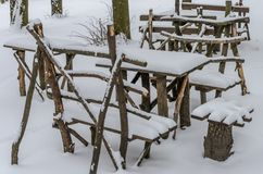 Wooden tables and chairs - furniture for a picnic handmade, stand among snow-covered woods strewn with snow Royalty Free Stock Photography