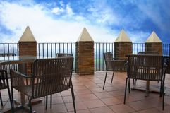Wooden tables and chairs on the large terrace, blue sky royalty free stock photos