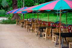 Beach cafe with wooden tables and chairs under colorful umbrellas. Wooden tables and chairs standing on the beach sand in Thailand stock photo