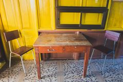 Wooden tables and classic wooden chairs are placed on yellow wooden walls Royalty Free Stock Photos