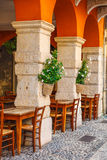 Wooden tables of comfortable outdoor cafe in Verona. Wooden tables of comfortable outdoor cafe ristorante among ancient columns and archs at Verona streets Royalty Free Stock Photography