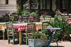 Wooden tables with green chairs at traditional Greek cafe Royalty Free Stock Image