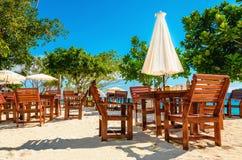 Wooden tables with sun umbrellas at beach royalty free stock photos