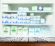 Wooden tabletop with blurred pharmacy or medicine shelf stock photography