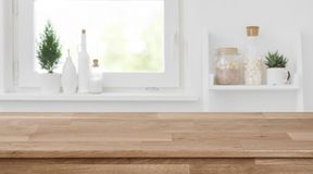 Wooden tabletop in front of blurred kitchen window, shelves background.  stock image