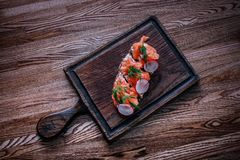 A wooden tabletop on which lies a board of sandwiches with salmon greens. royalty free stock image