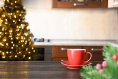 Free Wooden Tabletop With Red Cup Of Coffee And Blurred Christmas Kitchen Royalty Free Stock Photos - 202988588