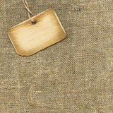 Wooden tag on sacking. An old worn wooden tag over a sacking background stock images