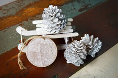 Wooden tag with toy christmas sleigh and pinecones Stock Photos