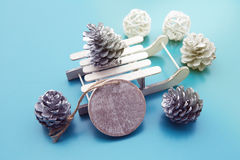 Wooden tag with toy sleigh and pinecones Royalty Free Stock Images