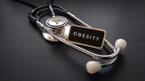 Wooden tag written with OBESITY and stethoscope on black background. Medical and Healthcare Concept stock image