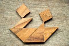 Wooden tangram puzzle in cou่ple sailing the boat shape background. (Concept for love and travel&#x29 royalty free stock photography