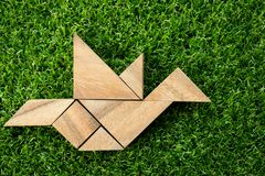 Wooden tangram puzzle in flying bird shape on artificial green g. Rass background (Concept of freedom, new experience or start entrepreneur&#x29 royalty free stock image