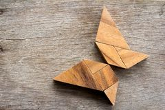 Wooden tangram puzzle in flying butterfly shape. Background royalty free stock photo