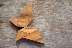 Wooden tangram puzzle in flying butterfly shape. Background stock photo